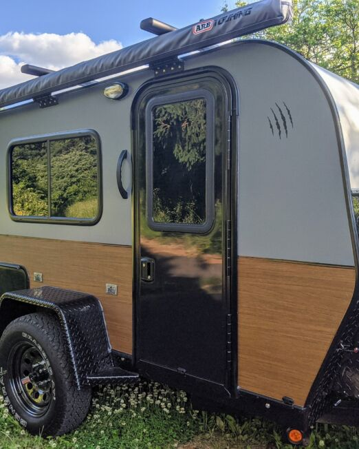 "Kodiak shown with optional Adventure edition package, roof rack + awning, and 24"" wood vinyl wrap"